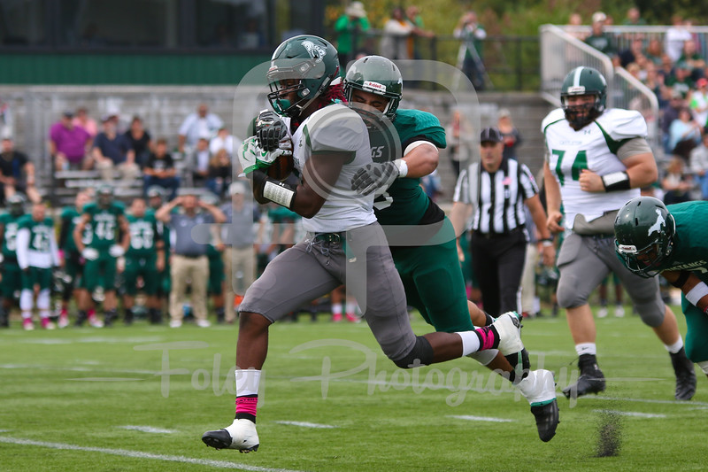Castleton University running back Moe Harris (1) Mount Ida Mustangs Sean Chinova (43)