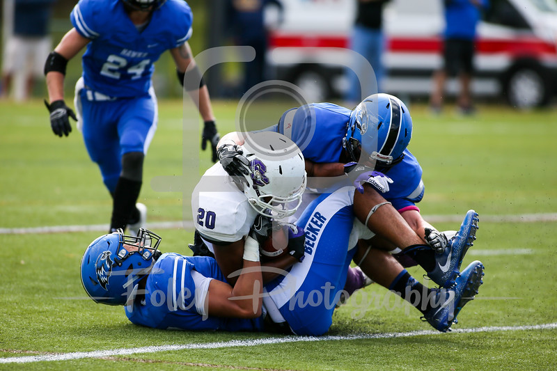 Curry College Colonels running back D'Aundray Burcy (20) Becker College Hawks linebacker Jared Zieman (39) Becker College Hawks linebacker Christian Perkins (10)