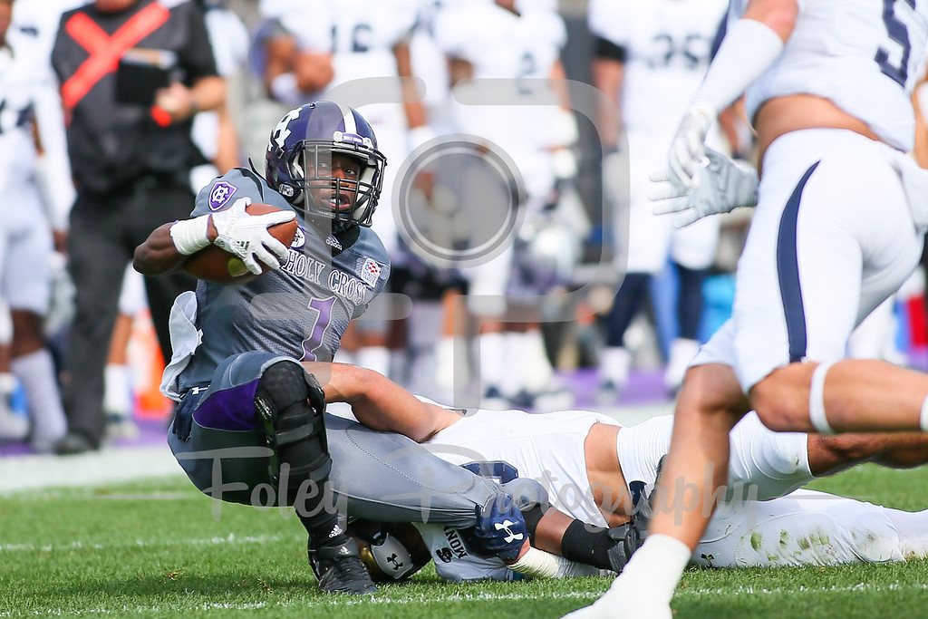 Monmouth Hawks defensive back Mike Basile (30) Holy Cross Crusaders running back Domenic Cozier (1)