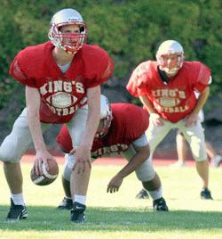 Enterprise/CHRIS GOODENOW<br /> King's quarterback Greg Uhrich calls audibles before a modified snap as he practices with two other teammates, Friday, August 26, 2005 at King's High School.