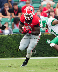 Georgia Bulldogs running back Keith Marshall (4), North Texas Mean Green defensive back Lairamie Lee (27), North Texas Mean Green defensive back Kenny Buyers (31)