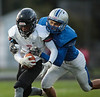 Fostoria's Bryan Stenson (7) looks to stiff arm Elmwood's Will Keiffer (20) as he is tackled out of bounds for a gain.