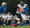 Fostoria's Keshawn Carter Stokes (20) catches, bobbles, then catches a pass down the middle of the field between Elmwood's Gunner Endicott (15) and Will Keiffer (20).