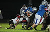 Elmwood's Mason Oliver (21) is tackled by Fostoria's Jacob Franklin (23) and Bryan Stenson.