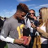 Odell autographs a ball for a fan while being interviewed by Laura Okmen.