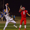 Exeter Monarch Julian Andalon (11) hauls in a touchdown catch over the outstretched arms of Lindsay Cardinal defender Juan Infante (8). Exeter won the season opener by a 42-14 score.