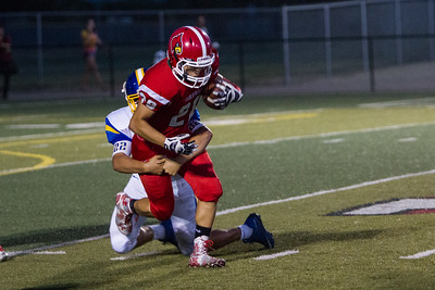 Lindsay Cardinal Ethan Duran (28) is wrapped up by Exeter Monarch linebacker Nico Torres (22) in the season opener for both teams. The Monarchs prevailed by 42-14 in this non-league contest.