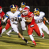Lindsay Cardinal Sal Rivera (5) attempts to elude Exeter's Garrett Parkinson (32) and Trystan Johnston (42) during their season opening contest. The Monarchs went on to win by a 42-14 score.