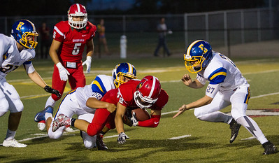Exeter Monarch defenders Brandon Freeman (21), Nico Torres (22), and Jacob Good (27) gang tackle Lindsay Cardinal Ethan Torres (28) as Cardinal Sal Rivera (5) looks on. The Exeter Monarch beat the Lindsay Cardinals 42-14 in the season opener for both teams.