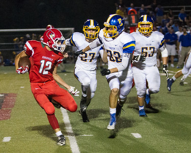 Lindsay Cardinal Bert Vasquez (12) attempts to elude Exeter Monarch defenders Jacob Good (27), Garrett Perkinson (32), and Anthony Perez (53). Exeter used its size and speed to wear down Lindsay in route to a 42-14 win.