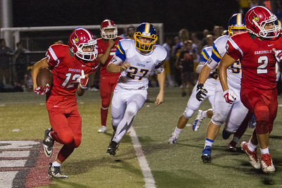 Lindsay Cardinal Bert Vasquez (12) runs the football against Exeter as Monarch Jacob Good (27) pursues.  The Monarch prevailed by a 42-14 score in the season opener for both teams.