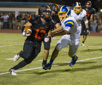Exeter went to 2-0 with a 26-13 win over the Woodlake Tigers.  Woodlake RB Alexander Marquez (13) attempts to elude the Exeter Monarch defenders.