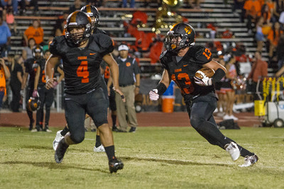 Exeter went to 2-0 with a 26-13 win over the Woodlake Tigers. Woodlake's Alexander Marquez (13) runs the football with Noah Garcia (4) leading the way.