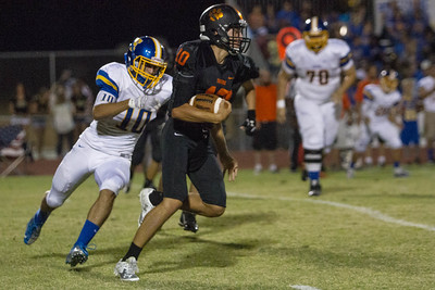 Exeter went to 2-0 with a 26-13 win over the Woodlake Tigers. Monarch DE Raul Jimenez (10) chases down Woodlake QB Eric Schwarz.