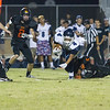 Woodlake cruised to a 55-27 victory over the visiting Farmersville Aztecs. Aztec RB Victor Castrejon  (4) tries to escape the shoelace tackle of Tiger LB Diego Ramirez (5).