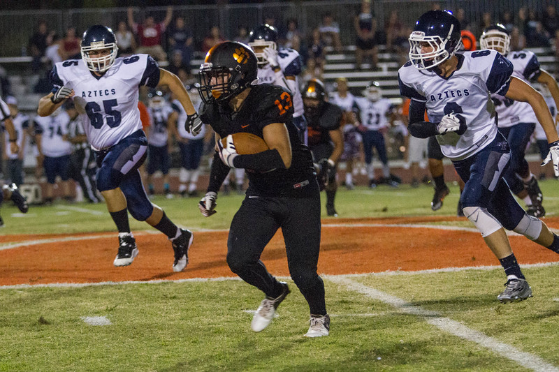 Woodlake cruised to a 55-27 victory over the visiting Farmersville Aztecs. Alexander Marquez (13) rushes past Farmersville defender Cody Bible (65) and Skyler Morris (6).