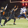 Woodlake cruised to a 55-27 victory over the visiting Farmersville Aztecs. Aztec QB J.J. Galaviz throws a pass over the outstretched arms on Woodlake defenders Joel Vasquez (55) and Marin Apodaca (82).