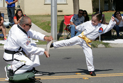 A Mid-California Tae Kwon Do member breaks a board as she walks down the parade route during the 2014 Woodlake Lions Club Rodeo Parade.