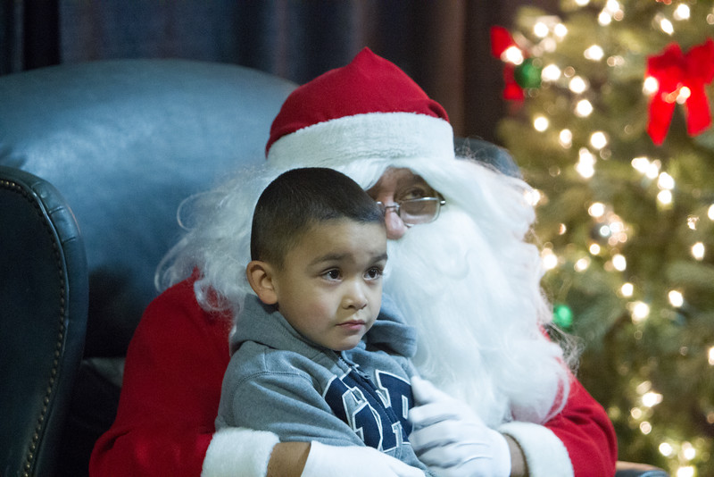 A young Lindsay resident poses with Santa Claus during the Lindsay Police Christmas Toy Giveaway.