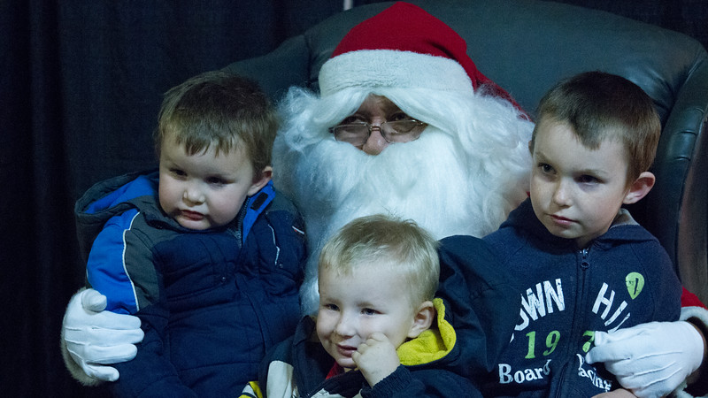Santa Claus poses for pictures with a family of boys at the annual Lindsay Police Christmas Toy giveaway.