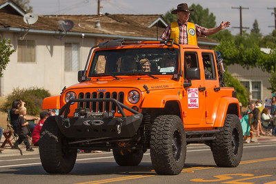 The Grand Marshal of the 2015 Woodlake Lions Rodeo Parade Stan Livingston wave to the crowds lining Valencia St.