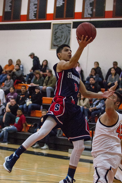 Strathmore scored a 71-55 league victory at Woodlake in each team's ESL opener.  Spartan Carlos Lopez goes for a lay up against Woodlake Tiger Arthur Reynoso (42).