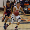 Strathmore scored a 71-55 league victory at Woodlake in each team's ESL opener. Tiger guard Jacob Valera (1) dribbles past Strathmore defender Seth Aparicio (1).