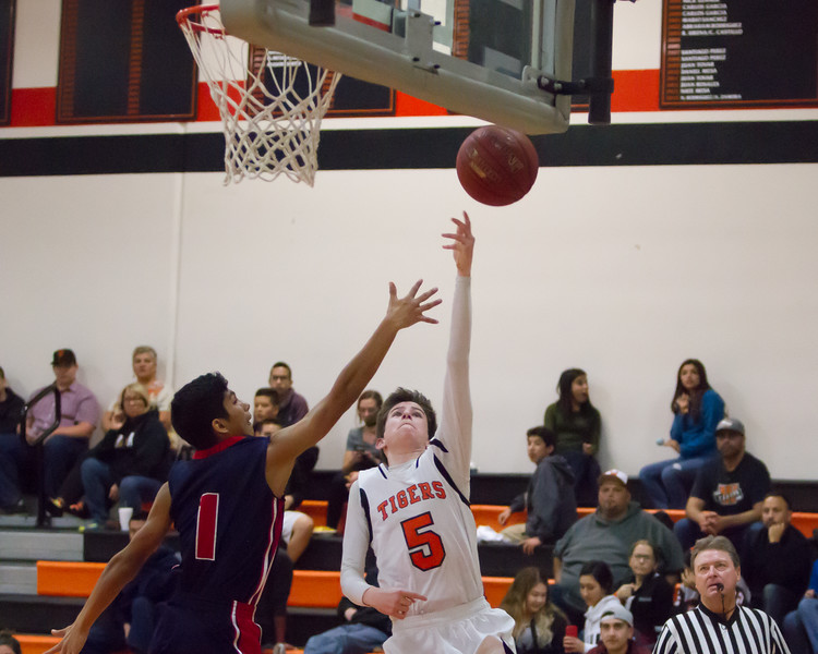 Strathmore scored a 71-55 league victory at Woodlake in each team's ESL opener. Woodlake Tiger guard Eli Thorn (5) shoots a lay-up over Strathmore point guard Seth Aparicio (1).