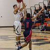 Strathmore scored a 71-55 league victory at Woodlake in each team's ESL opener. Woodlake Tiger guard Jacob Valera (1) attempts a 3-point shot against the out stretched arm of Strathmore Spartan defender Seth Aparicio (1).