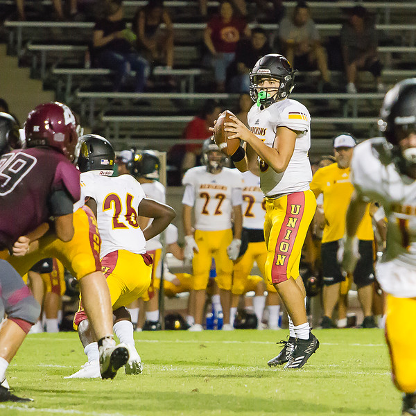 Tulare Union's QB, Jorge Gonzales (15) looks downfield for a receiver in Friday night's season opener against the Mount Whitney Pioneers. The Redskins would roll to a 57-6 victory.