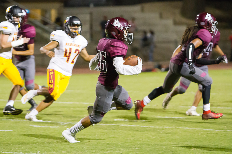 Mt. Whitney Pioneer Jayden Castellon (26) rushes for yardage againt the visiting Tulare Union Redskins at Visalia's Mineral King Bowl. Tulare Union came away with a 57-6 victory.