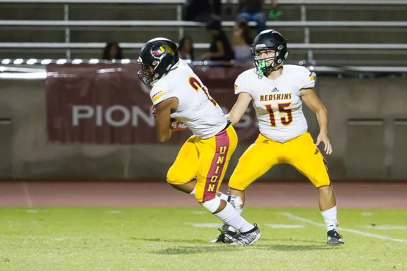 Tulare Union Quarterback Jorge Gonzalez (15) hands the football off to Redskin RB John White IV (2) in their season opening contest at Mt. Whitney.