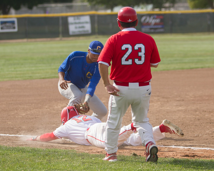 Lindsay Cardinal right fielder Robert Gomez dives back to 3rd base under a pick off attempt as Coach Kendig looks on. The Cardinals suffered a tough 5-3 extra innings loss to the Corcoran Panthers.