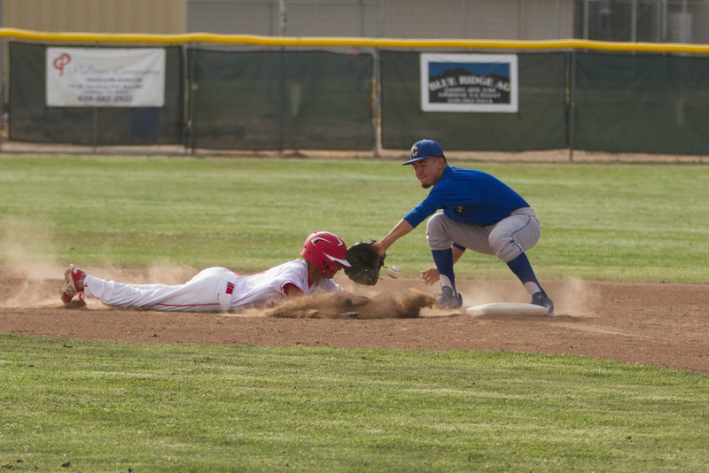 A Cardinal base runner survives a pick off attempt at second base as the baseball squirts out of the second baseman's glove. Corcoran was able to score 2 runs in the 8th inning to defeat the Lindsay Cardinals by a 5-3 score.