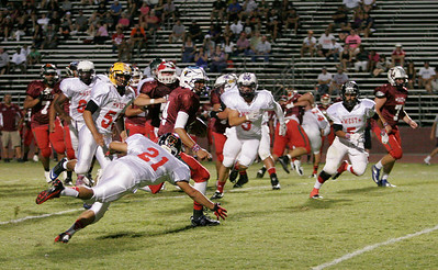 Quarterback Raul Alverez (14) of Redwood rushes the football as Victor Bonilla (21) attempts to make the tackle during the 46th Annual East vs. West Tulare-Kings All Star Football game on Saturday, June 22, 2013.