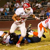 Lindsay RB Jacob Hernandez (4) leaves tacklers on the turf during the 47th Annual East vs. West Tulare-Kings Football All Star Game on July 25, 2014.