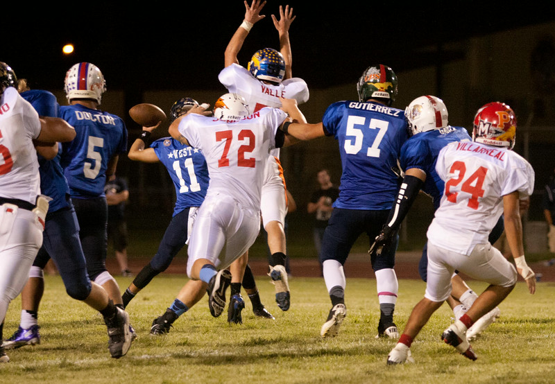 Exeter High's Matt Valle  (51) attempts to block a pass from Laton QB Manual Cruz (11) in the 47th Annual East vs. West  Tulare-Kings All-Star Football Game. The West prevailed 28-7 over the East.