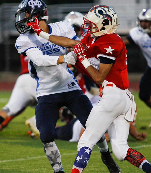 Strathmore DB Gilbert Acevedo (R, in red) tangles with Mission Oaks WR John Bridges (in white) during the 50th edition of the East vs. West Tulare-Kings All-Star Football Game held on Saturday at Visalia Community Stadium.