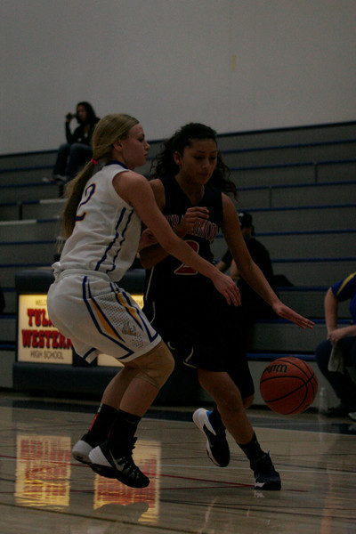 Strathmore's Mariah Hernandez (2) attempts to drive around Exeter's Jacque Hutcheson in the contest during the 5th Annual Tulare Mid-Winter Showcase Invitational BasketballTournament.