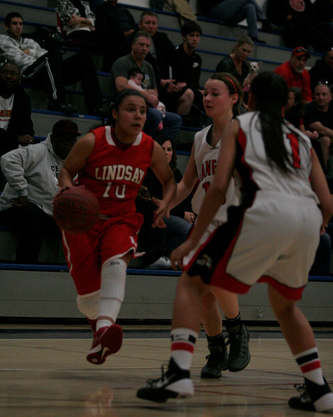 Linsday's Christina Castro (10) dribbles toward Hanford's Janelle Sumilong (11) during their quarter final game in the 5th Annual Tulare Mid-Winter Showcase Invitational Basketball Tournament.