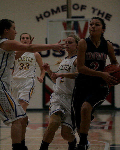 Strathmore Spartan Mariah Hernandez takes the basketball up against the Exeter defender in the Consolation Semi-Final game at the 5th Annual Tulare Mid-Winter Showcase Basketball Tournament.