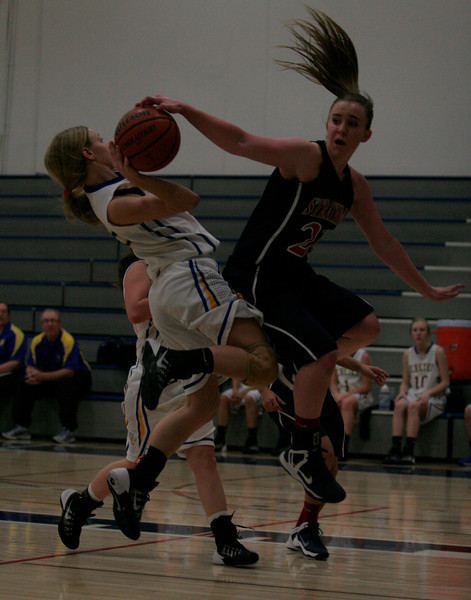 Strathmore Spartan Shelby Vanasen (21) attempts to block Jacqueline Hutcheson (2) shot during the consulation semi-final contest.