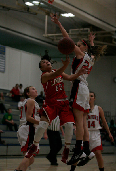 Lindsay G Christina Castro (10) drive for a lay up against Hanford PG Brooke Johnson (24) during the 5th Annual Tulare Mid-Winter Showcase.