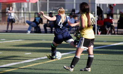 Strathmore all-star Taylor Brown kick the ball down field in the 5th Annual Tulare & Kings County Soccer All-Star game as goal keeper Alex Benevides, of Porterville High School looks on.