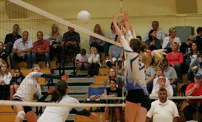Exeter Monarchs Gabi Crookshanks (5) and Chelsea Laron (7) attempt to block a CVC spike in Friday's match.