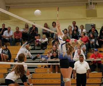 Exeter Monarchs Olivia Harden and Chelsea Larson attempt to block a Central Valley Christian spike by Veronica Nederend (4) on Friday, October 10, 2013.