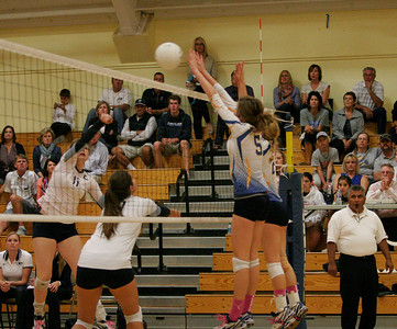 Central Valley Christian Cavalier Madalyn Souza (11) attempt to spike the volleyball against Exeter Monarchs Gabi Crookshank (5) and Jacque Hutchenson (2) during their match on Friday, October 10, 2013.