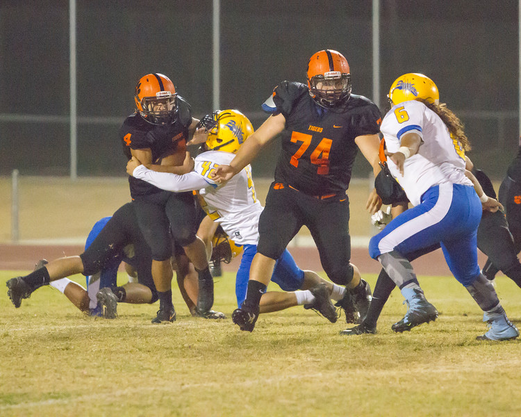 Woodlake Tiger RB Noe Garcia (4) attempts to escape the tackle of Corcoran NG Leonard Rodriguez (42) during their East Sequoia League contest at Woodlake. The Tigers scored the winning touchdown with 10.9 seconds left on the clock and garnered a 28-27 win.