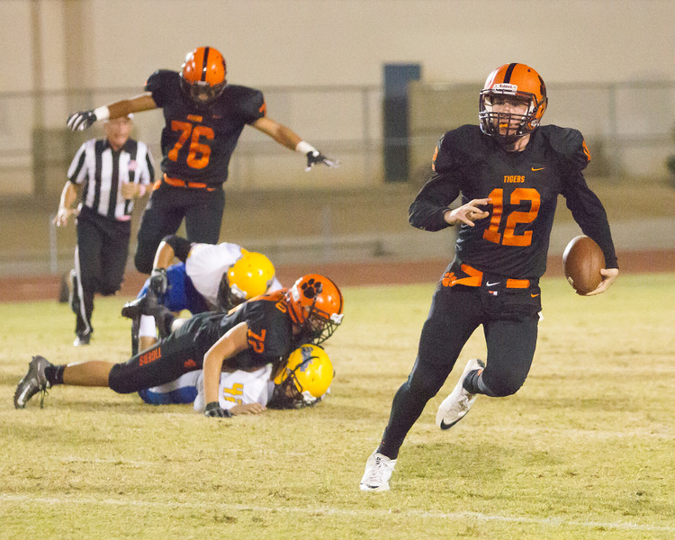 Robert Stevenson (12) Woodlake's QB rushes the football as Tiger Angel Castillo (72) puts a pancake block on a Corcoran Panther defender. Woodlake prevailed in the ESL contest by a 28-27 score.