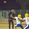 Robert Stevenson, Woodlake's sophomore QB throws a pass over Corcoran Panther defenders Gilbert Martinez (60) and Juan Perez (51). The Tigers scored a come from behind 28-27 victory over the visiting Corcoran Panthers.